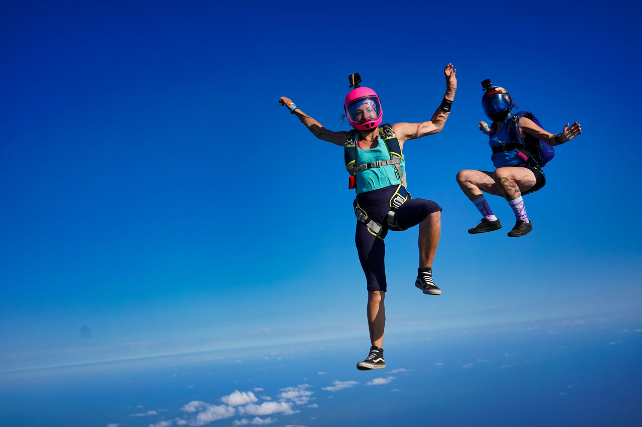 A licensed skydiver in a pink helmet and a licensed skydiver in a black helmet in freefall fly in a head up orientation