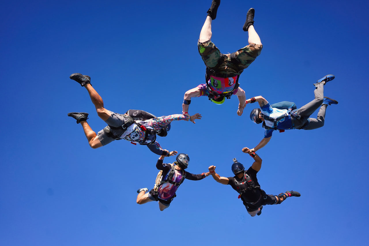 Five licensed skydivers form a round formation in the sky above Oak Island, NC