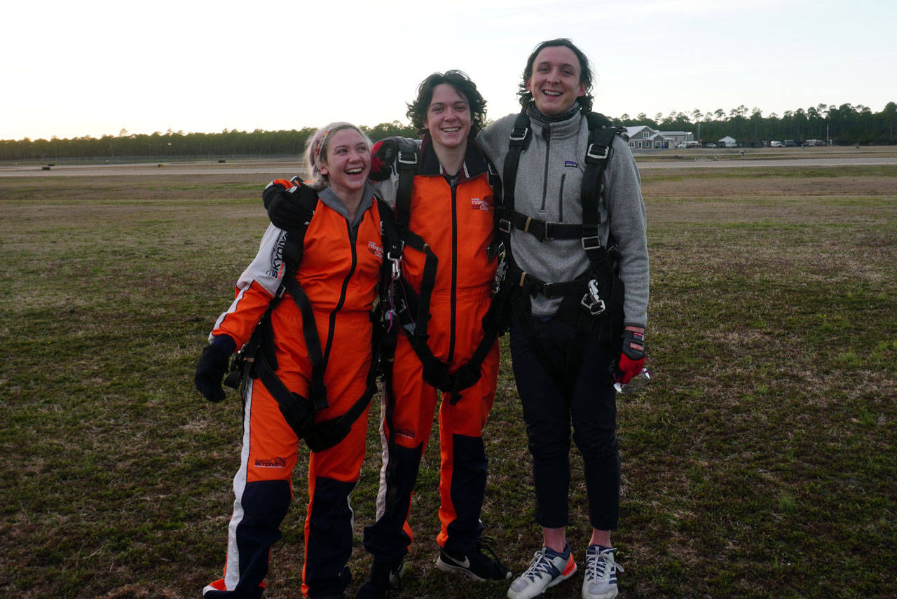 Three smiling tandem students in harnesses pose for a picture