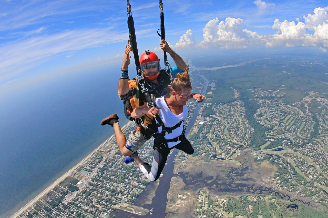 Tandem skydiving instructor and tandem student in mid transition from falling stomach relative to earth to an upright position beneath the deploying parachute above the coast of Wilmington, NC