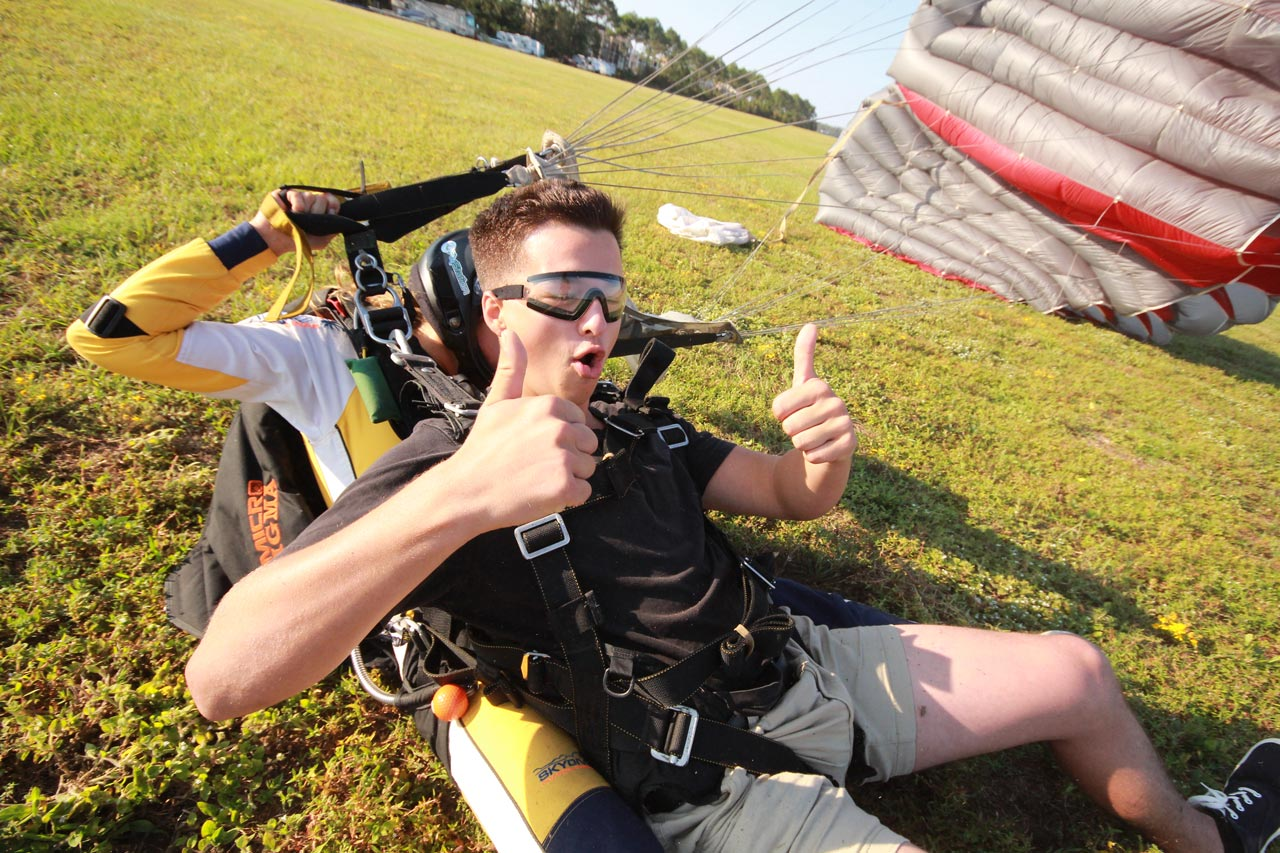 Tandem student in black rimmed goggles gives two thumbs up moments after a slide in landing as the tandem instructor collapses the tandem parachute