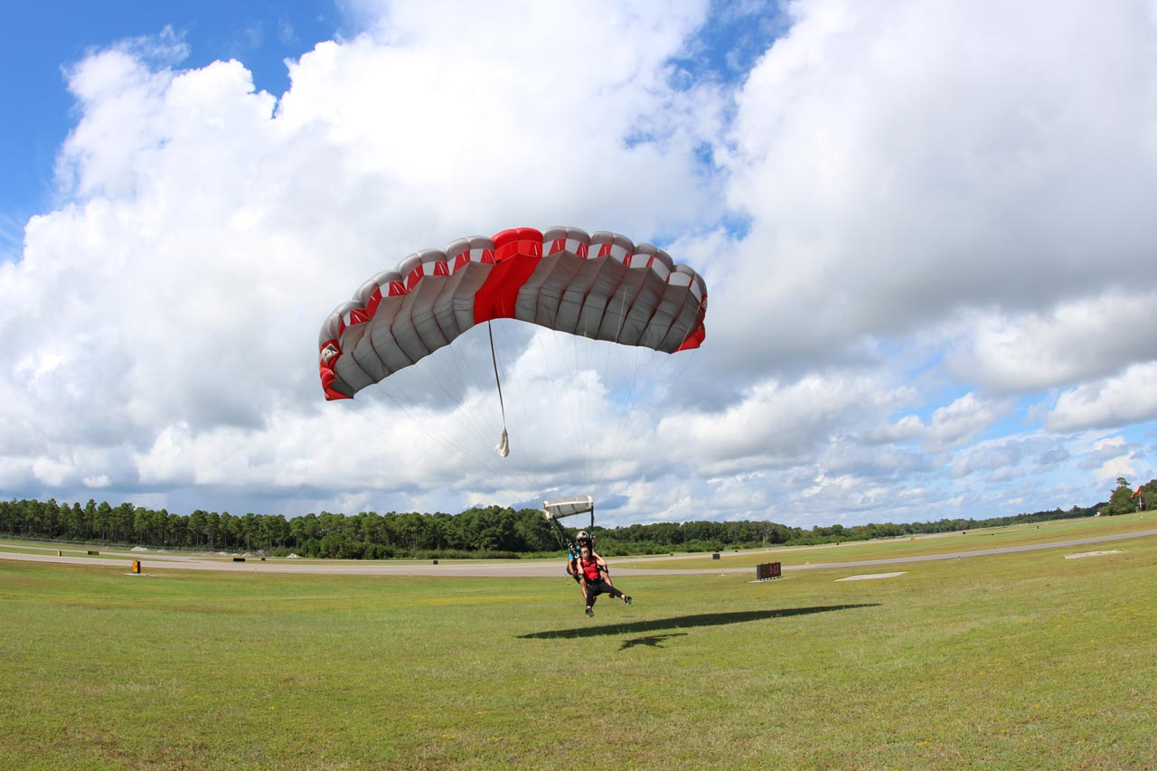 Tandem instructor and tandem student slide in landing beneath a gray parachute with a red center cell