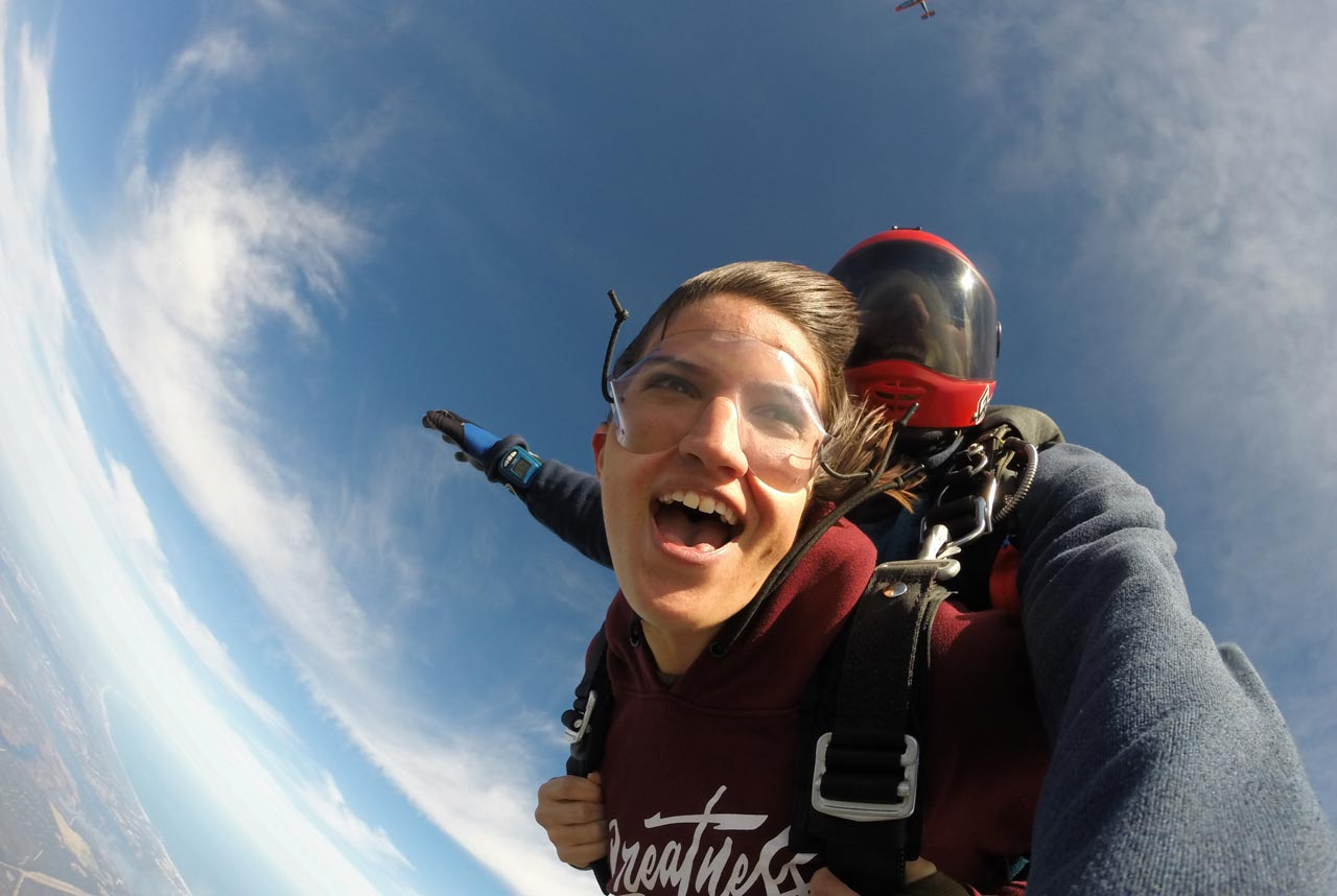 Tandem skydiving student and instructor in freefall with the tail of the plane barely visible behind them