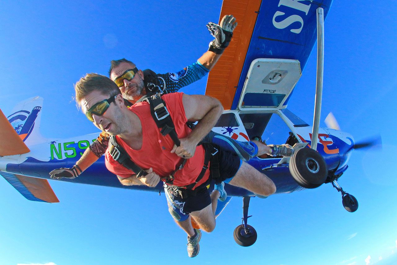 Tandem skydiving student in red tee shirt and gym shorts and tandem skydiving instructor exit Cessna 182 named Sharky