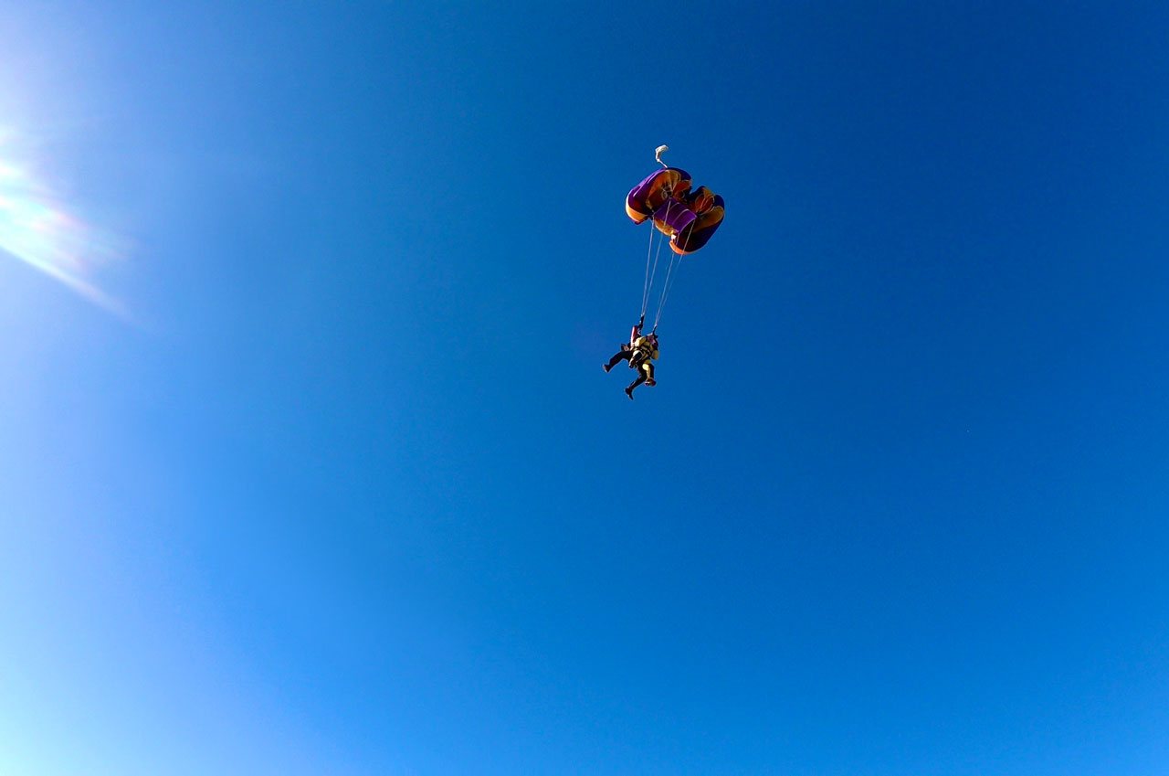 Tandem skydiving pair suspended beneath purple and orange parachute in the middle of the deployment sequence