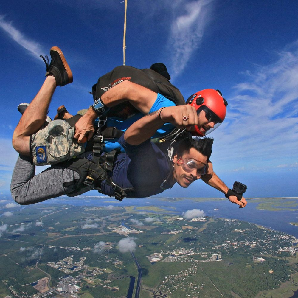 Outside photo of tandem skydiver and instructor in freefall over Wilmington, NC