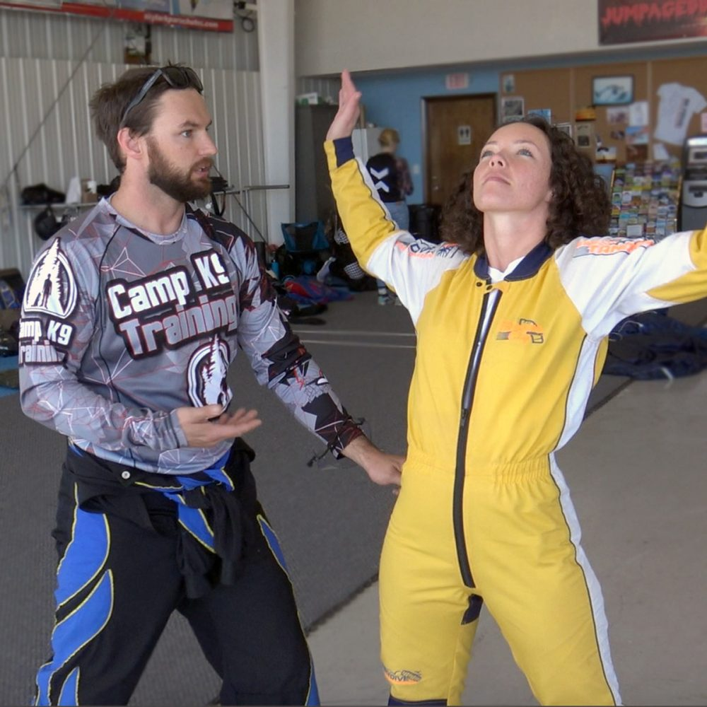 Curly haired female skydiving student in yellow jump suit practices her arch body position as skydiving instructor provides instruction