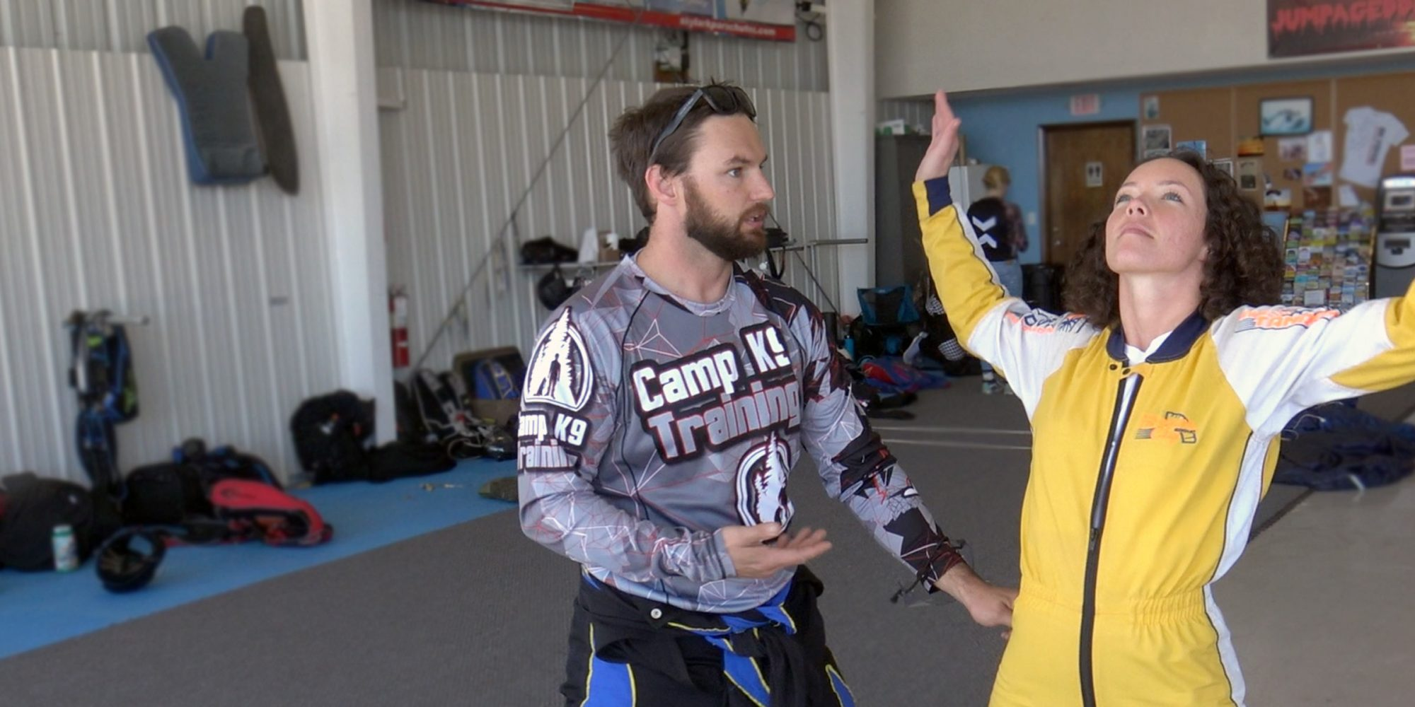 Curly haired female skydiving student in yellow jump suit practices her arch body position as skydiving instructor provides instruction before skydiving in Wilmington, NC