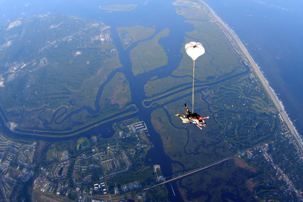 Top view of tandem skydiving pair in freefall with the drogue inflated over the intracoastal waterway of Oak Island, NC