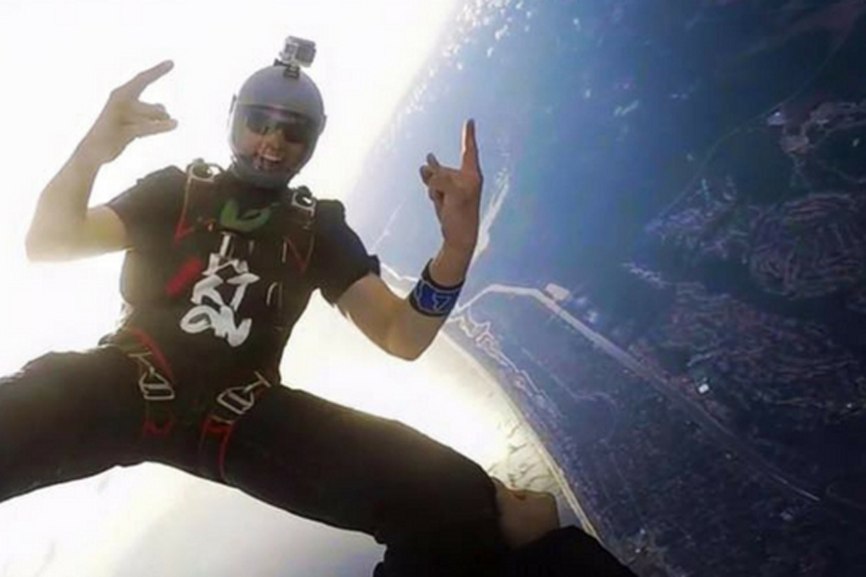 Exuberant licensed skydiver in a gray helmet holds up both hands with the rock on gesture