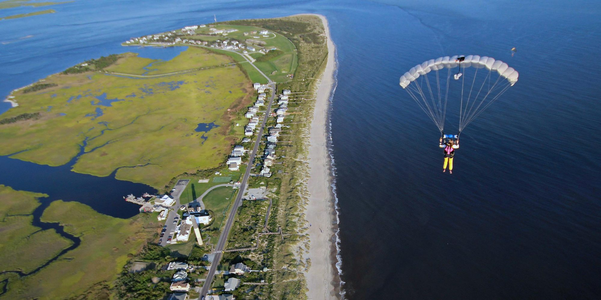 Solo skydiver under white parachute flying over the coast of Oak Island, NC
