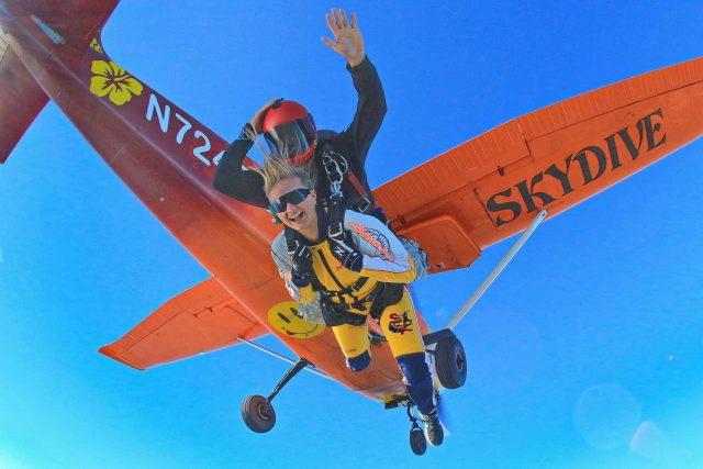 A tandem skydiving student and instructor moments after they exit the orange Cessna 182 aircraft named bubbles. The underside of the aircraft has a yellow smiley face with its tongue sticking out and the word skydive under the wing.