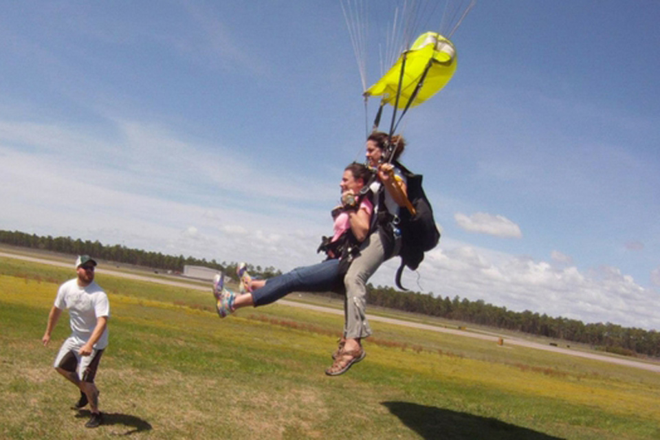 Female tandem skydiving instructor and female student beneath a parachute lift their legs preparing to slide in for landing