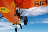 Underside view of orange Cessna-182 with skydiver seated in door giving shaka gesture with left hand