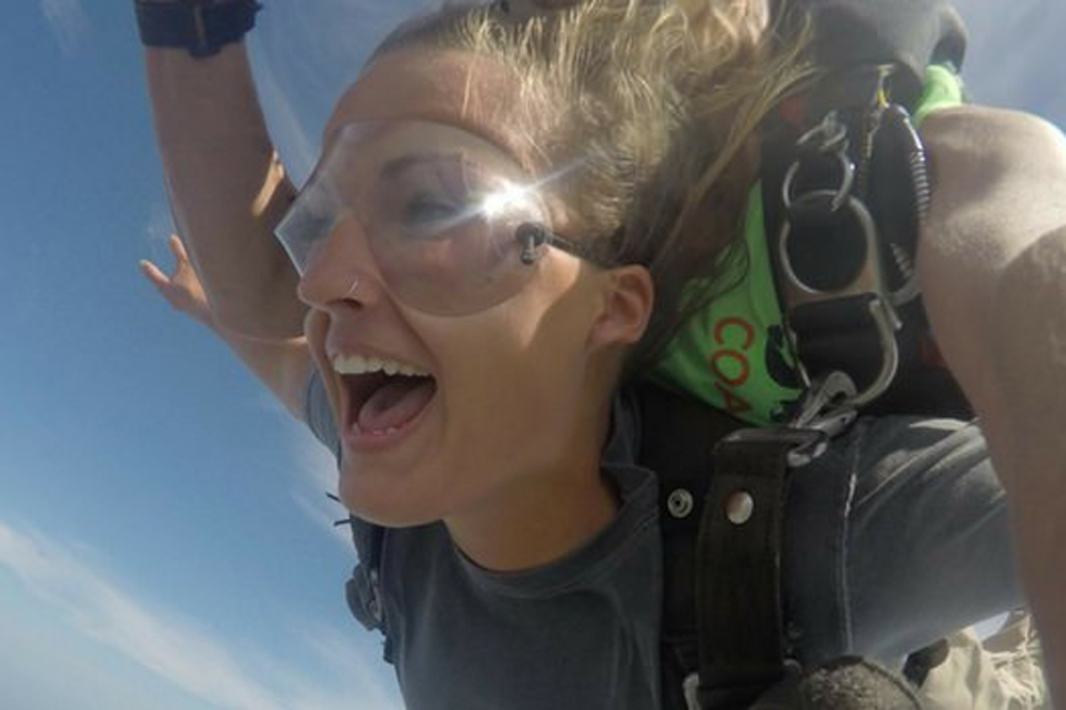 Young female tandem skydiver with hoop nose ring lets out an exhilarated whoop
