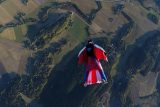A licensed skydiver in a red white and blue wingsuit flies over a patchwork of green fields