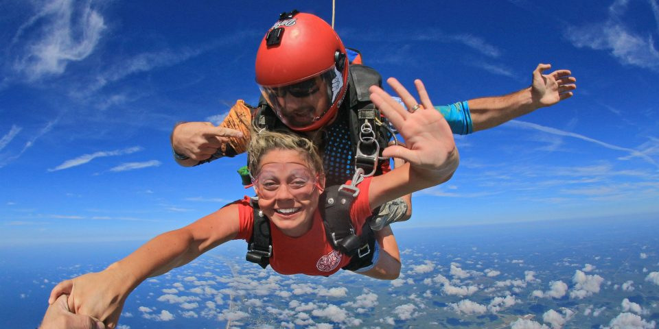 Tandem skydiving instructor in red helmet points at tandem skydiving student as she grabs the skydiving videographers hand and gestures for a high-five with the other during freefall