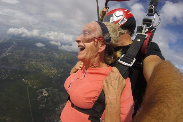 Older female tandem skydiving student with inspired expression takes in the view beneath canopy